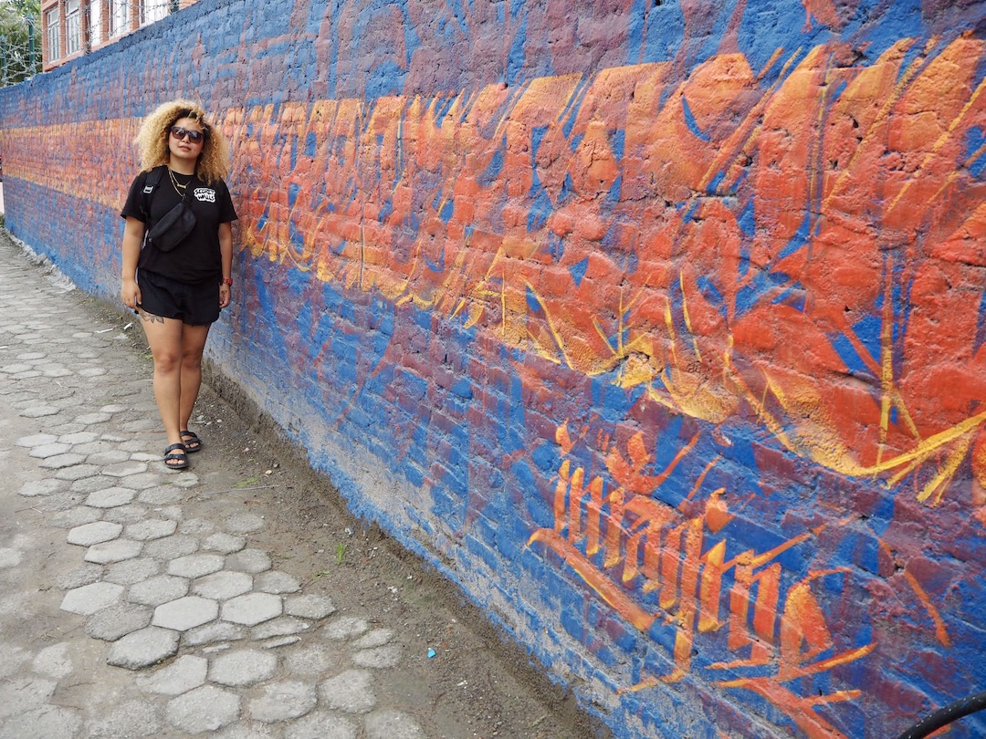 Streetart in Kathmandu: Sneha Shrestha alias Imagine vor ihrem Werk